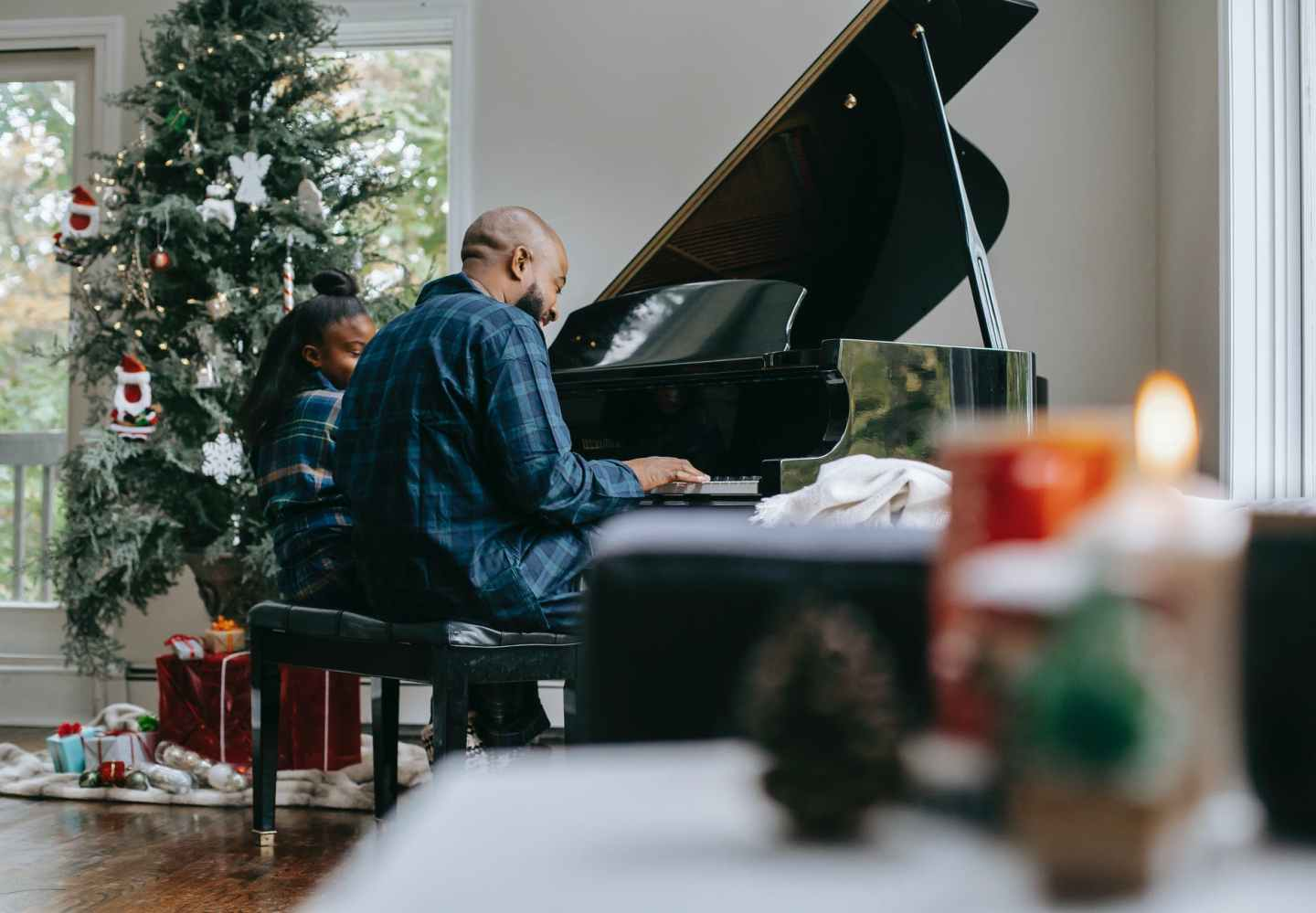 black father playing piano with little daughter