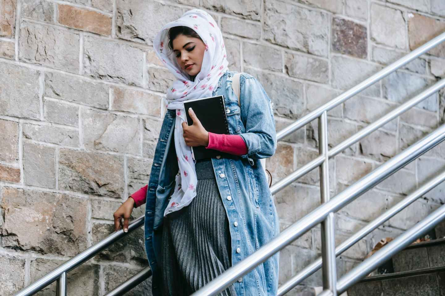 calm young woman in hijab walking downstairs with planner