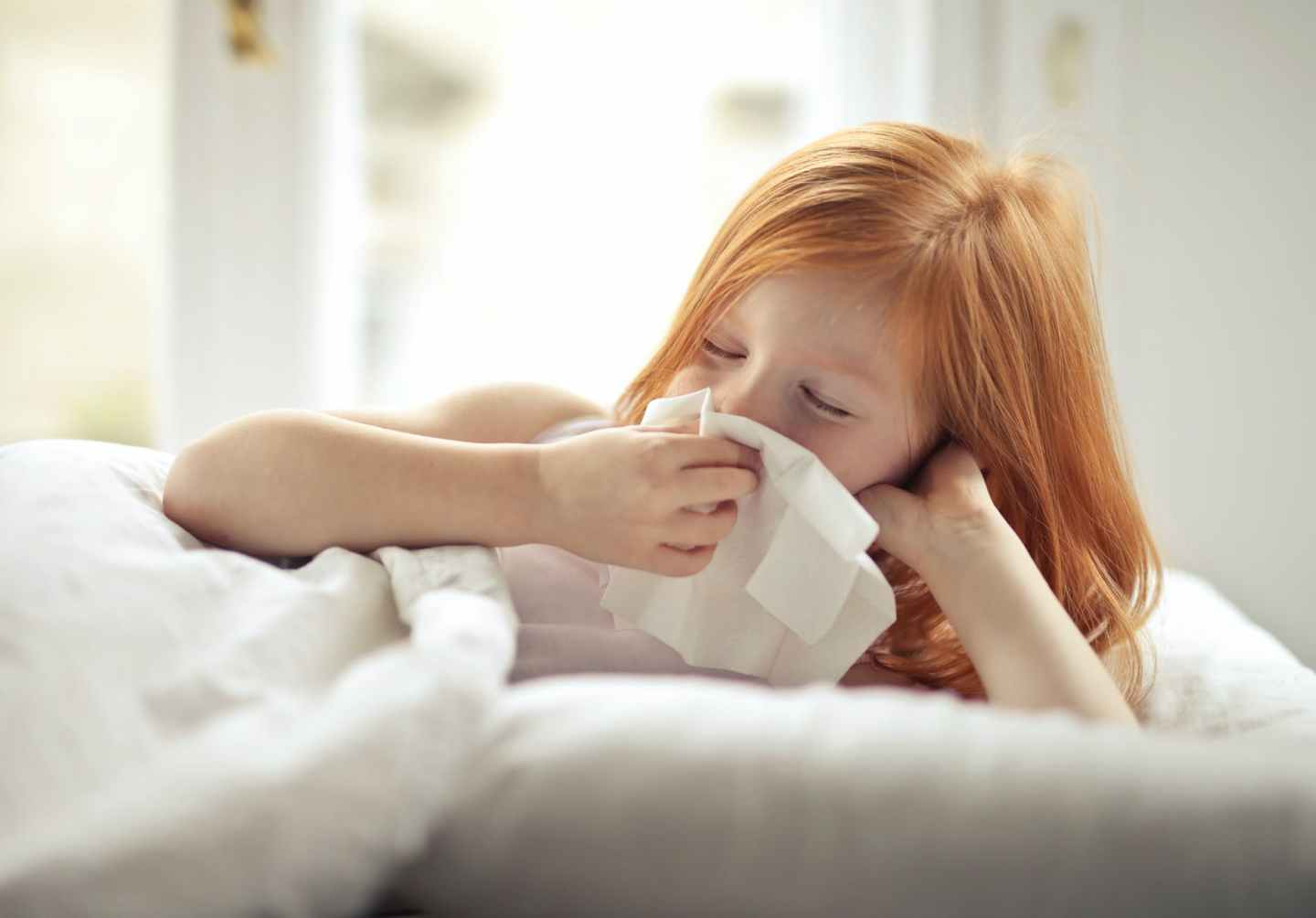 ill preteen girl wiping snot while resting in bed at home