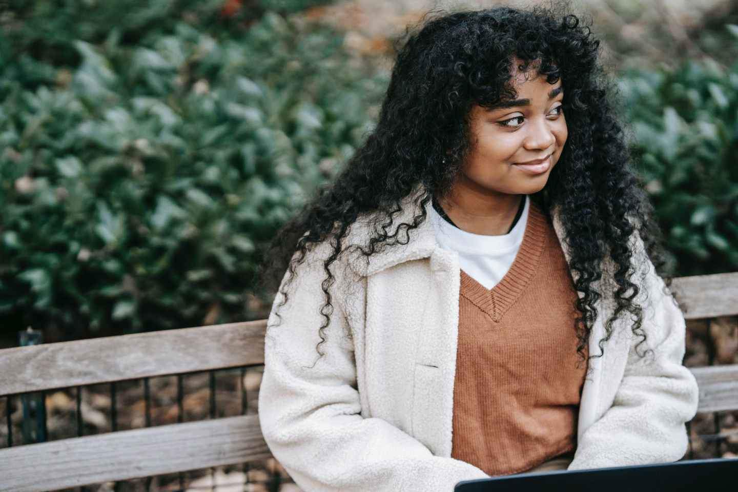 smiling black woman with laptop sitting in city park