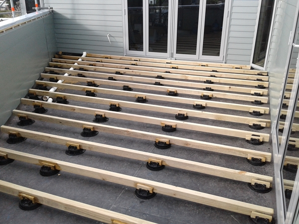 a timber deck on adjustable height pedestals is being built over the EPDM
