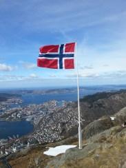 """Norweska flaga dumnie powiewa nad Bergen z wysokości góry Ulriken (643 m n.p.m.), na którą dostałem się kolejką linową Ulriksbanen za """"jedyne"""" 155 koron norweskich w obie strony (w przeliczeniu na złotówki to ok. 80 zł)."""
