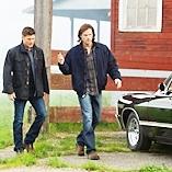 Dean and Sam walk by the Impala.