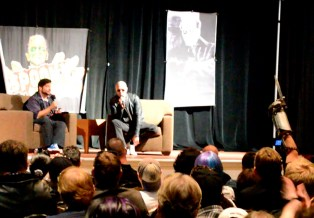 Rooker on stage with Merle hand up in salute_FB