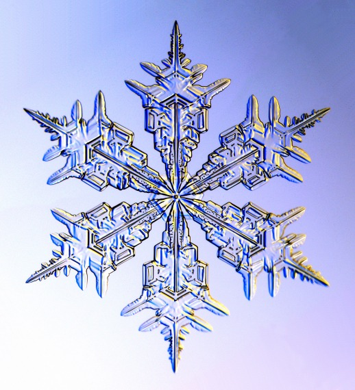 Image description: Clear snowflake against a blue background.