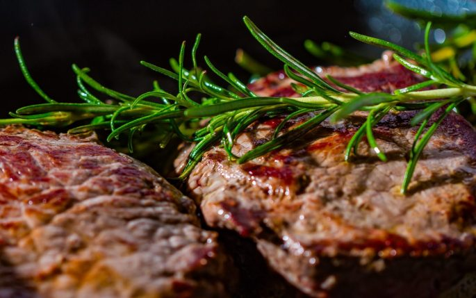Two cooked steaks with a sprig of rosemary laid across them.