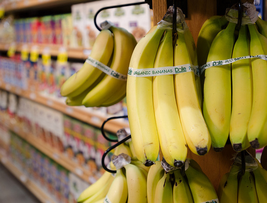 Yellow bananas with an organic food label hanging in front of a cereal aisle in a grocery store.