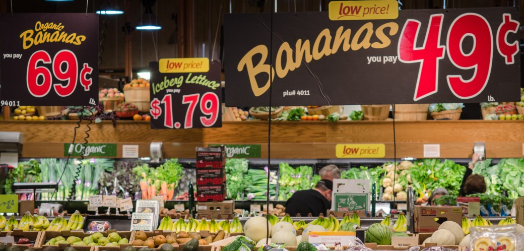 Produce section with many food labels at a grocery store in Virginia. Bananas on display are 49 cents a pound for conventional or 69 cents a pound for organic.