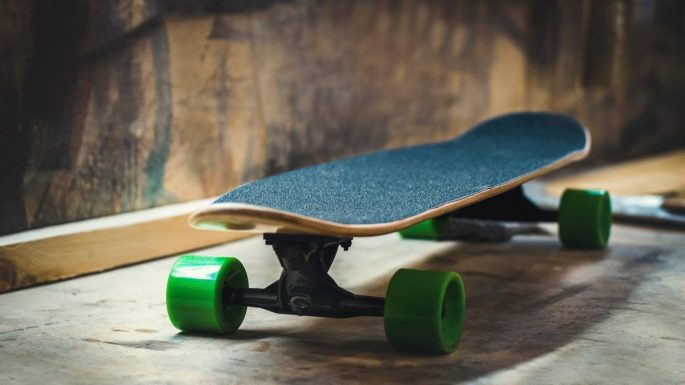 Close range image of a skateboard, showing the rough surface of the top of board and bright green plastic wheels. The skateboard sits on a rough wood surface.