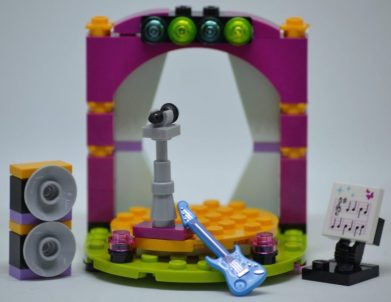 Brightly colored rock and roll stage with speakers, sheet music, electric guitar, microphone stand, and lights - all made out of lego bricks.