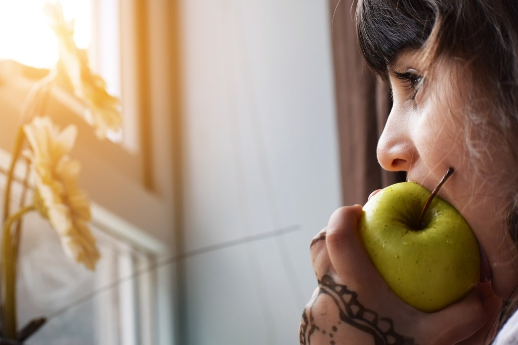 Child, dark hair, eating apple near window