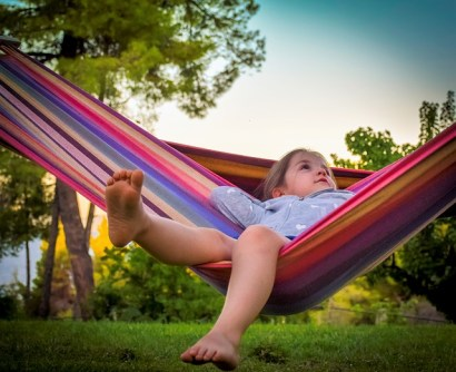 child in colorful hammock outdoors