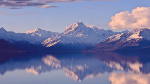snow-covered mountains and fluffy clouds reflected in still water