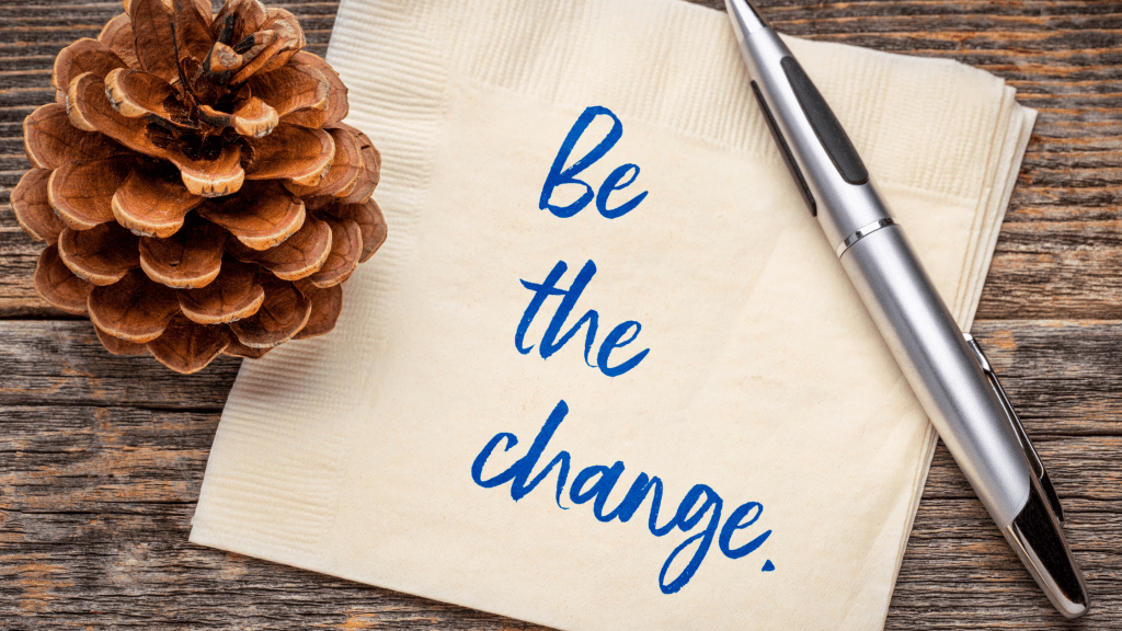 """Pinecone, pen, and napkin on a desk, with the words, """"Be the change"""" written on the napkin."""