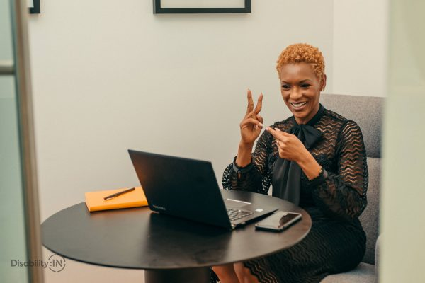 African American woman smiling at a computer and signing in ASL