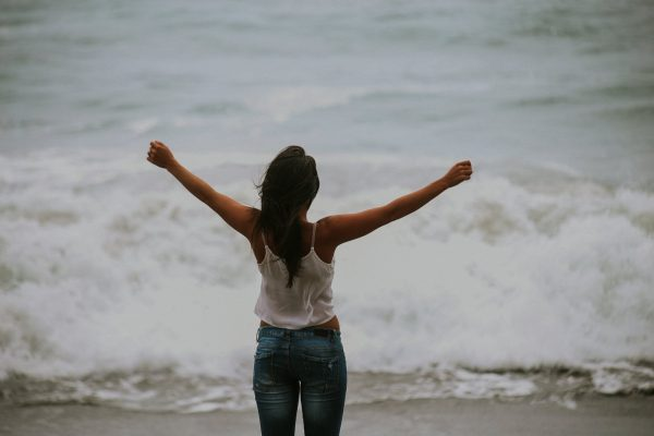 Woman standing on the seashore with arms outstretched. She's learning jeans and a white tank top.