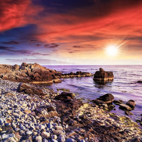 the sun sets over the water near a rocky coastline, casting an orange and purple glow