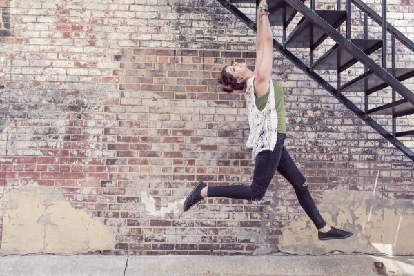a woman playfully grabs onto the underside of a metal staircase next to a brick wall, swinging her feet beneath her