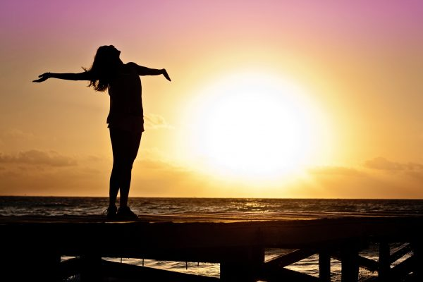 silhouette of a woman with her arms outstretched on a beach at sunrise