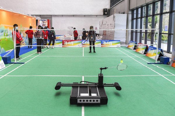 Visitors playing badminton with robots