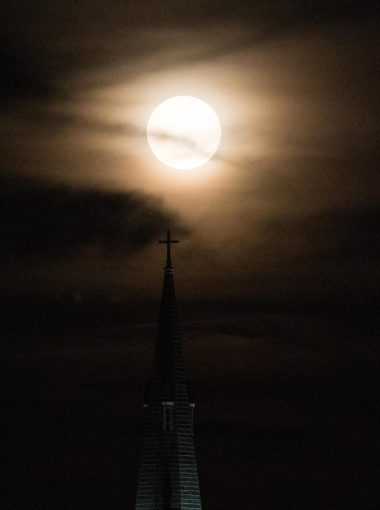 The moon rises behind the tower of the Santo Domingo church