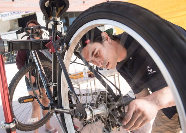Keith Edmonds, a bike mechanic at 2 Wheeler Dealer in Brea, tunes up a student's bike during the Sustainable Transportation Expo's Bike Fest -- one of the Earth Week events at Cal State Fullerton -- on Thursday. (Photo by Nick Agro, Orange County Register/SCNG)