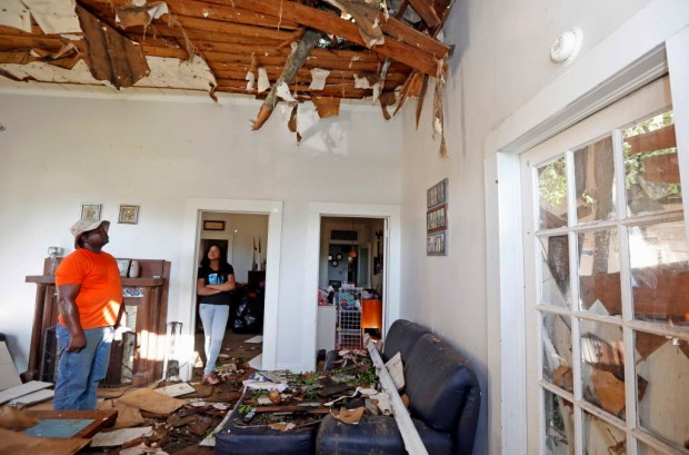 Michael Williams, left, and his daughter Kayshia Williams survey the damage to their cousin's home after a storm in Durant, Miss., Monday, May 1, 2017. A small Mississippi town clobbered by an apparent tornado during fierce weekend storms could be without power for days, authorities said Monday. (AP Photo/Rogelio V. Solis) ORG XMIT: MSRS116