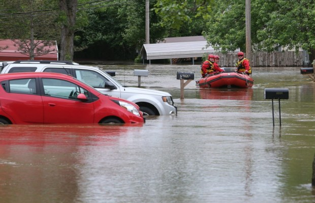 Members of the High Ridge fire department take a boat in at the Village Green Estates trailer park on Monday, May 1, 2017, in Cedar Hill, Mo. Torrential rains over the weekend caused flash flooding across Missouri, and as storm drains and fields continue to pour into rivers, they continue to rise. (J.B. Forbes/St. Louis Post-Dispatch via AP) ORG XMIT: MOSTP203