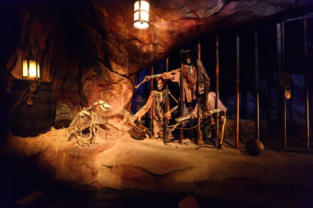 """Three skeleton pirates try to coax a key from a skeleton dog on the Shanghai Disneyland version of the """"Pirates of the Caribbean: Battle for the Sunken Treasure"""" attraction. (File photo by Jeff Gritchen, Orange County Register/SCNG)"""