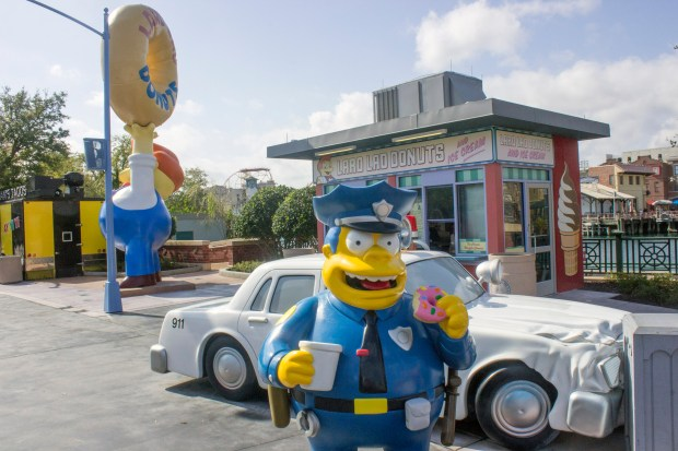 """Chief Wiggins of the Springfield Police Department has in his hands one of his favorite foods, the large pink donut from Lard Lad Donuts in the town of Springfield is based on """"The Simpsons"""" cartoon series and is at the Universal Studios Florida theme park. (Photo by Mark Eades, Orange County Register/SCNG)"""
