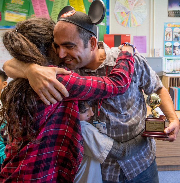 Vincent Saporito gets a hug from his daughter, Marie Saporito, as they squish his son, Francis Saporito, after he was surprised with a 2018 Teacher of the Year award from the Orange County Department of Education in Huntington Beach, California, on Tuesday, May 2, 2017. Saporito, is a special education teacher for the deaf and hard of hearing at College View Elementary School, is one of six teachers who were surprised with the honor by county superintendent of school Dr. Al Mijares. (Photo by Jeff Gritchen, Orange County Register/SCNG)