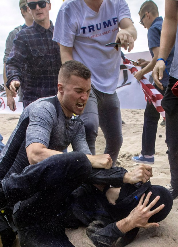 A Trump supporter, and an anti-Trump protester, in black, end up in fisticufs as the two sides come together in Huntington Beach, CA on Saturday, March 25, 2017. The protester ended the fight after using pepper spray. (Photo by Mindy Schauer, Orange County Register/SCNG)