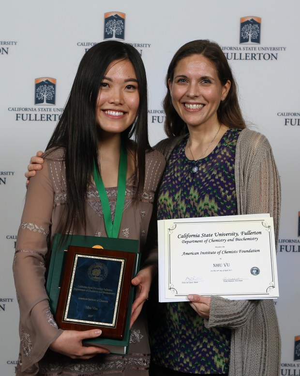 Cal State Fullerton student Nhu Vu, accompanied by associate professor Paula Hudson, receives awards at the Natural Sciences and Mathematics Awards banquet on April 20. (Photo courtesy of Greg Andersen)