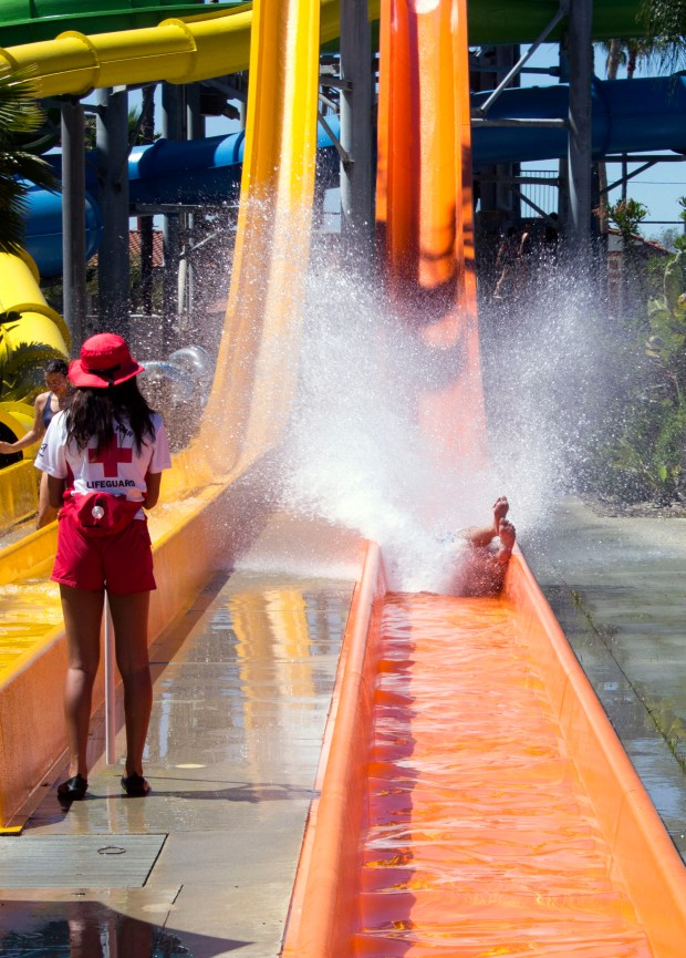 Nothing but feet are visible on one of the water slides when a person reaches bottom under the watchful eye of one of the lifeguards at Knott's Soak City Water Park. (Photo by Mark Eades, Orange County Register/SCNG)