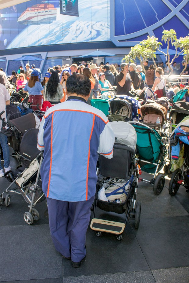 A cast member in Tomorrowland at Disneyland has the task of keeping the parked strollers organized in neat rows as they take up much of the walking space beneath the old, unused, Peoplemover tracks near the entrances to the Star Tours and Buzz Lightyear attractions. (Photo by Mark Eades, Orange County Register/SCNG)