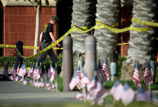 An investigator works the site of a mass shooting at the Inland Regional Center on Monday, Dec. 7, 2015 in San Bernardino, Calif. The FBI said it's investigating the massacre on Wednesday in San Bernardino, Calif., that killed dozens as a terrorist attack. (AP Photo/Jae C. Hong)