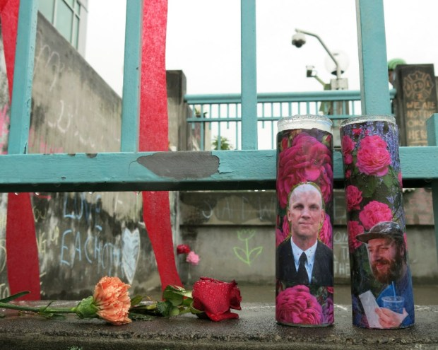 Votive candles bearing the photos of two men who were fatally stabbed on a Portland, Ore., light-train while trying to stop another man from harassing two young women with an anti-Muslim tirade, sit on a rain-soaked memorial on Tuesday, May 30, 2107 in Portland. Taliesin Myrddin Namkai-Meche, 23, and Ricky Best, 53, died in the attack. The suspect, Jeremy Joseph Christian, 35, made a first court appearance on charges of aggravated murder and attempted murder Tuesday in a Portland, Oregon courthouse. (AP Photo/Gillian Flaccus) ORG XMIT: RPGF201
