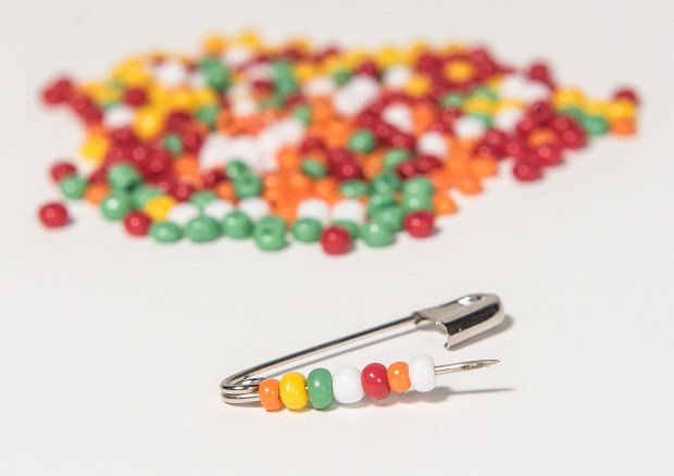 Step 1 on how to make a safety pin bracelet: Push open a safety pin, string beads on it and push it closed. Repeat until you have enough decorated safety pins to wrap around your wrist. Tuesday, April 25, 2017. (Photo by Nick Agro, Orange County Register/SCNG)