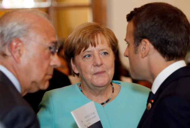 German Chancellor Angela Merkel, center, speaks with French President Emmanuel Macron, right, and Secretary-General of the Organisation of Economic Co-operation and Development Angel Gurria as they attend a round table meeting of G7 leaders and Outreach partners at the Hotel San Domenico during a G7 summit in Taormina, Italy, Saturday, May 27, 2017. Leaders of the G7 wrap up their meeting on Saturday with discussions focused on terrorism, climate and trade. (AP Photo/Domenico Stinellis) ORG XMIT: VLM107