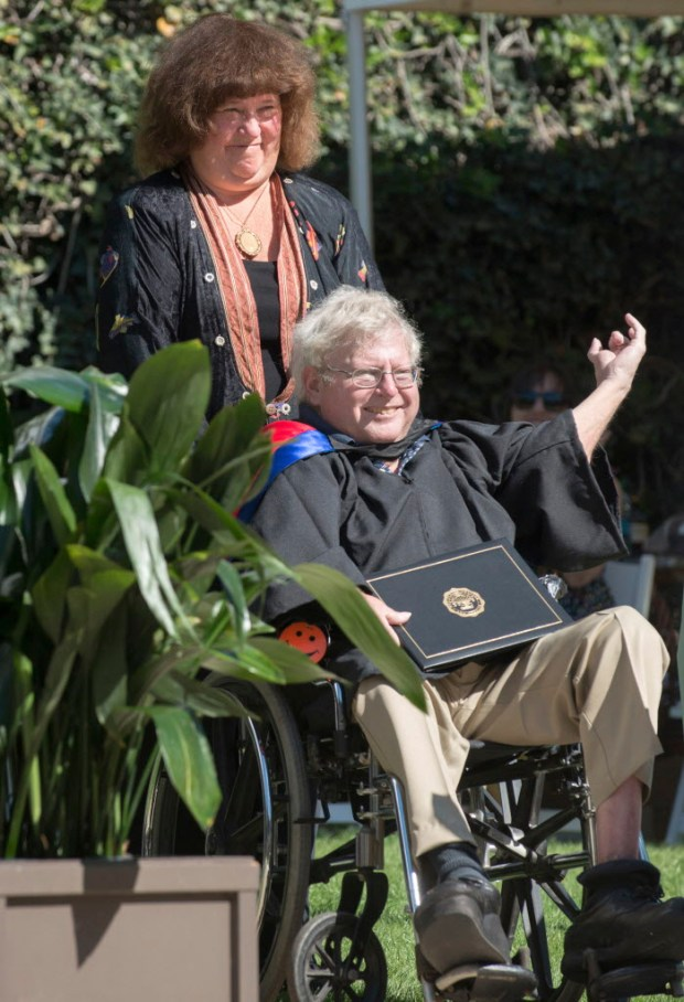 In this Sunday, May 21, 2017, photo provided by Occidental College Occidental College professor Roger Boesche and his wife Mandy acknowledging a standing ovation at Occidental's 2017 Commencement in Los Angeles. Boesche, who was credited by Barack Obama with sparking the future president's interest in politics, died on Tuesday, May 23, at age 69. He had retired from Occidental on Sunday after 40 years on the faculty. (Marc Campos/Occidental College via AP) ORG XMIT: LA403