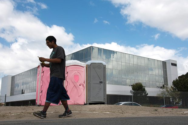 A homeless man walks back to his tent after using portable toilets that were installed on the Santa Ana River trail near Rampart and Orangewood in Anaheim on Monday, May 15. (Photo by Ken Steinhardt, Orange County Register/SCNG)