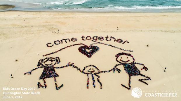 """More than 1,500 kids, parents and volunteers joined forces Thursday for a beach cleanup in Huntington Beach, followed by an """"aerial art"""" message to celebrate Kids' Ocean Day. /COURTESY ORANGE COUNTY COASTKEEPERS"""