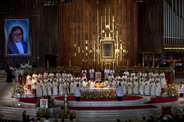 Priests participate in the beatification ceremony for the late sister Maria Ines Teresa Arias, whose photograph hangs at left, in the Basilica of Our Lady of Guadalupe in Mexico City, Saturday, April 21, 2012. The Mexican nun, who founded the Congregation of Poor Clare Missionary Sisters, was beatified at the Basilica on Saturday. Beatification is a first step toward sainthood. (AP Photo/Dieu Nalio Chery)