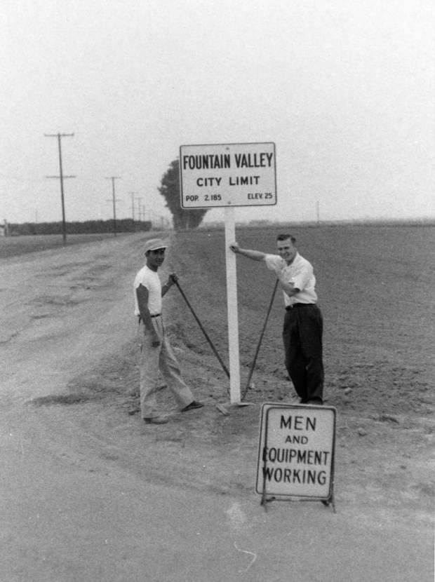 Fountain Valley's first mayor James Kanno, left, and city employee Bud Klecker install one of the early city limit signs in Fountain Valley. (Photo courtesy of Fountain Valley Historical Society)