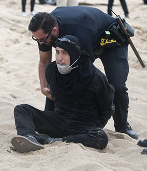 An anti-Trump protester is taken into custody at a pro-Trump march in Huntington Beach on Saturday, March 25, 2017. Groups such as Antifa (which stands for anti-fascism) are also creating anxiety among experts who study extremist movements. Even though the group is small and splintered, a violent wing of the group has been stepping up its recruitment efforts, said Brian Levin, whoheads the Center for the Study of Hate and Extremism at Calstate San Bernardino. (Photo by Mindy Schauer, Orange County Register/SCNG)