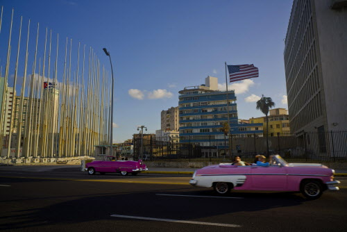 In this Jan. 12 file photo, tourists ride in classic American convertible cars past the United States embassy, right, in Havana, Cuba. On Friday, June 16, President Donald Trump is expected to give America's Cuba policy its second 180-degree spin in three years. Speaking from Miami, Trump's expected to revive the Cold War goal of starving Cuba's communist system of cash while inciting the population to overthrow it. (AP Photo/Ramon Espinosa, File)