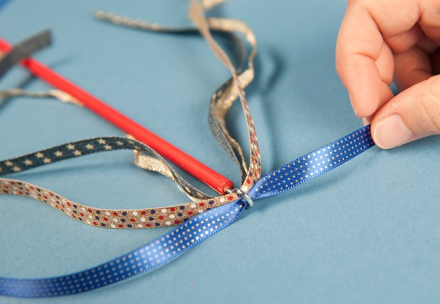 Step 4: Thread the ribbons through the hole of each eye screw. If you squeeze in as many ribbons as you can, you won't need to tie any knots. Wednesday, May 31, 2017. (Photo by Nick Agro, Orange County Register/SCNG)