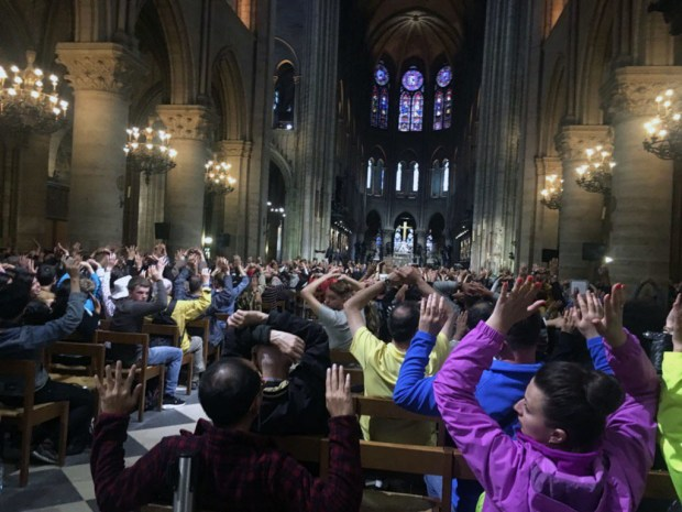 "In this image provided by Nancy Soderberg, people inside Notre Dame cathedral sit with their hands in the air, after an attack on police in Paris, Tuesday, June 6, 2017. Paris prosecutors have opened a counterterrorism investigation after an unidentified assailant attacked police with a hammer outside Notre Dame Cathedral. French Interior Minister Gerard Collomb says the attacker cried ""it's for Syria"" as he went after officers patrolling an esplanade in front of the famous landmark. (Nancy Soderberg via AP) ORG XMIT: LON147"