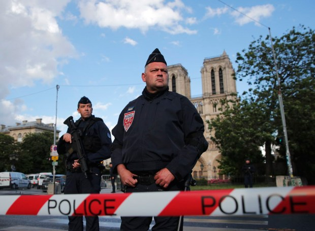 Police officers seal off the access to Notre Dame cathedral, seen in the background, after a man attacked officers with a hammer outside the famous landmark, in Paris, France, Tuesday, June 6, 2017. The Paris prosecutor's office said the investigation was opened Tuesday soon after the attack. The attacker was shot and wounded in the incident in one of France's most popular tourist areas. (AP Photo/Christophe Ena) ORG XMIT: REB134