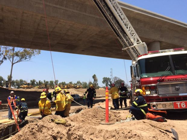 Firefighters work to hoist up an injured worker after he fell into a trench at a construction site Friday, June 2. (Photo Courtesy of the Orange County Fire Authority)